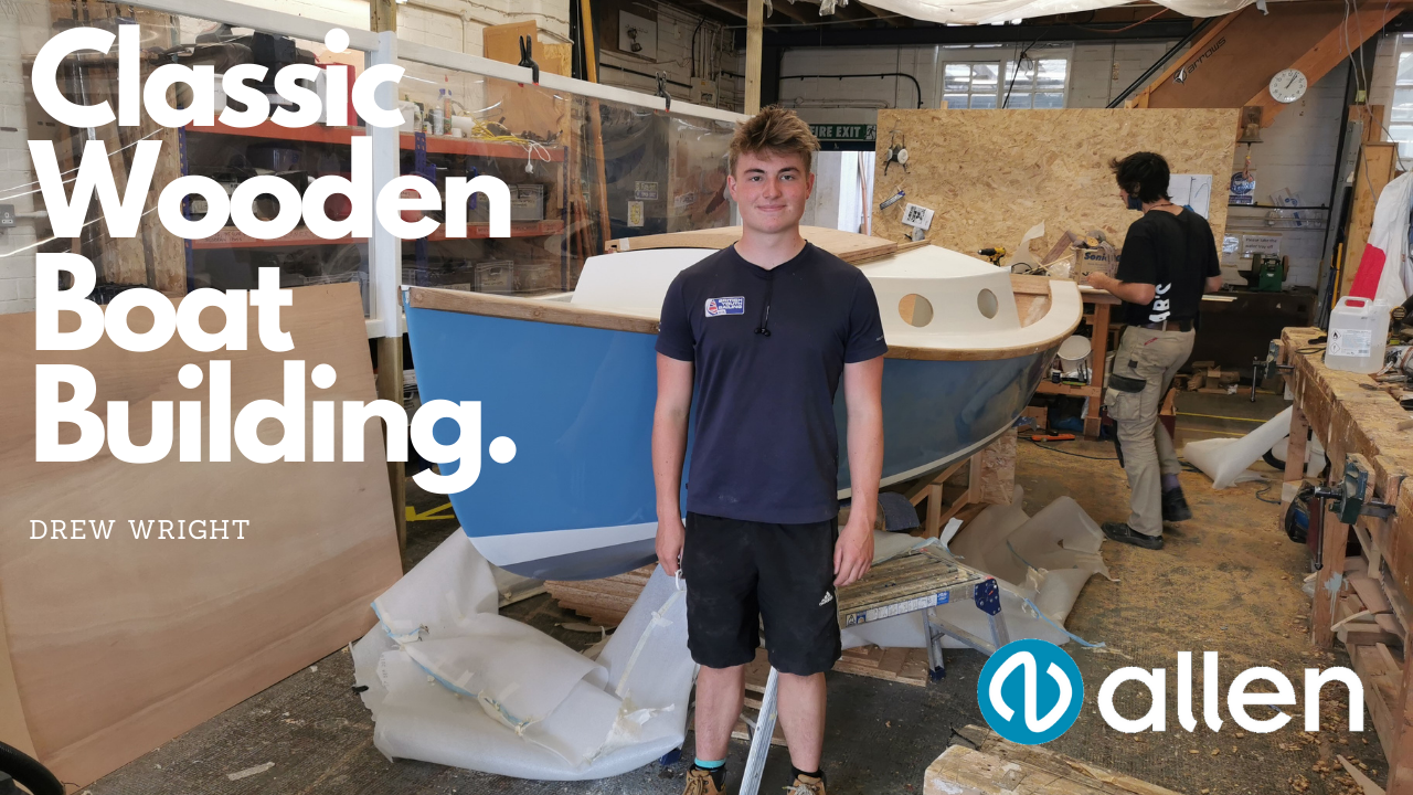 Drew Wright standign in front of this hand made plywood cabin cruiser.