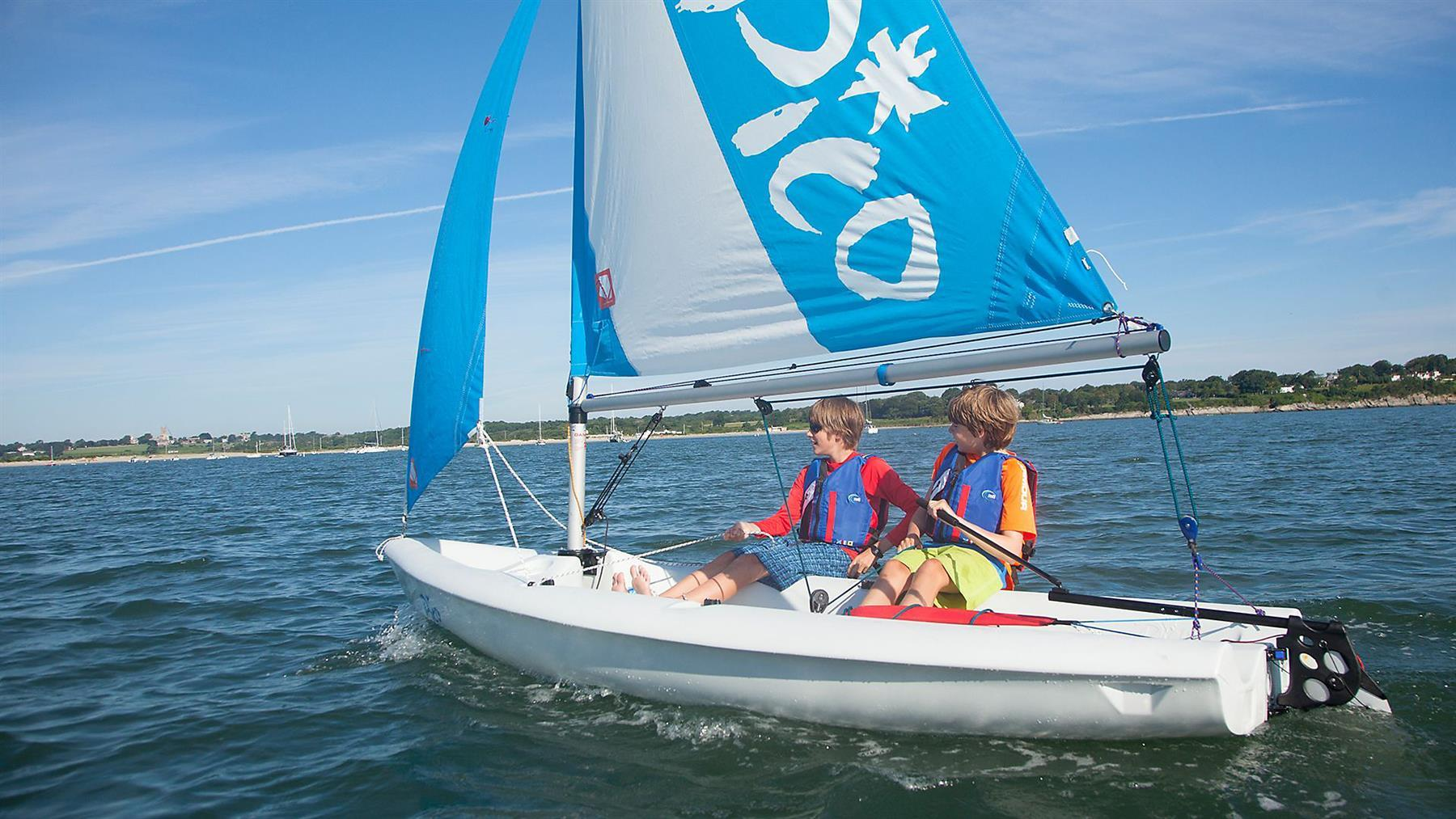 Laser Pico sailing on calm waters with two young boys.
